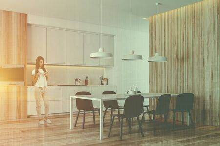 Young woman standing in modern kitchen with white and wooden walls, white countertops and dining table and chairs. Toned image double exposure Reklamní fotografie