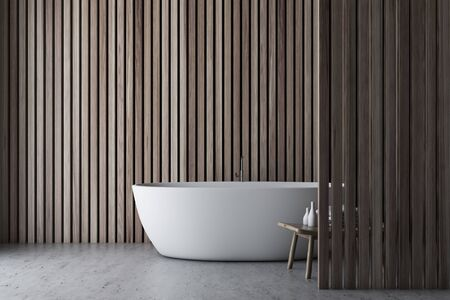 Interior of light wooden minimalistic bathroom with concrete floor, white bathtub and chair with towels and shampoos. 3d rendering Banco de Imagens