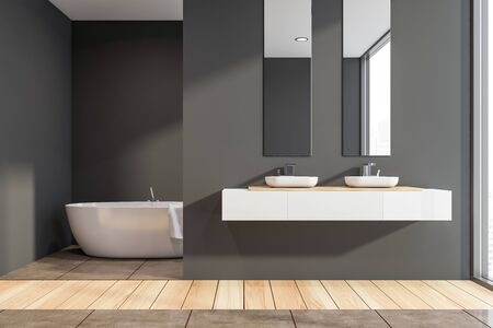 Interior of stylish bathroom with dark gray walls, wooden and tiled floor, two sinks standing on white countertop with vertical mirrors above it and and bathtub in background. 3d rendering