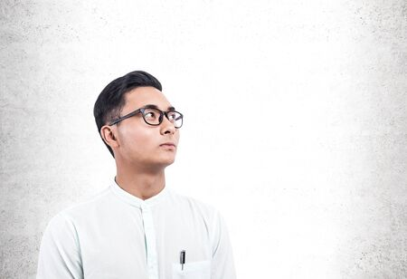 Portrait of serious young Asian businessman wearing white shirt and glasses and looking upwards standing near concrete wall. Concept of planning. Mock up