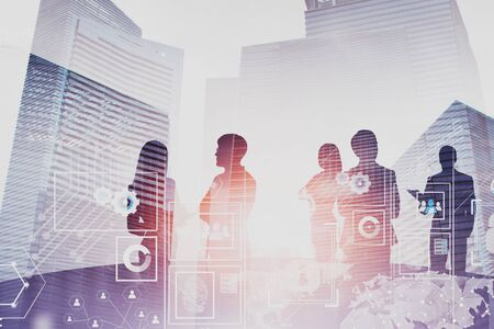 Silhouettes of business people brainstorming near round office table over cityscape background with double exposure of futuristic business interface. Concept of hi tech. Toned image Stockfoto