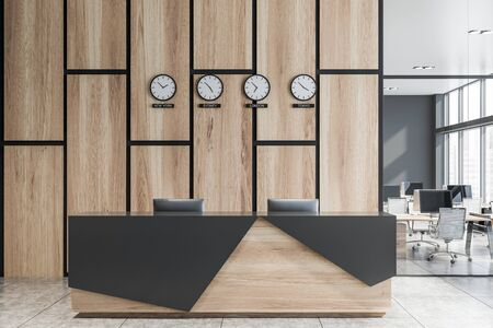 Wooden and gray reception table with computers standing in modern open space office with gray and wooden walls and clocks showing world time. 3d rendering Banco de Imagens