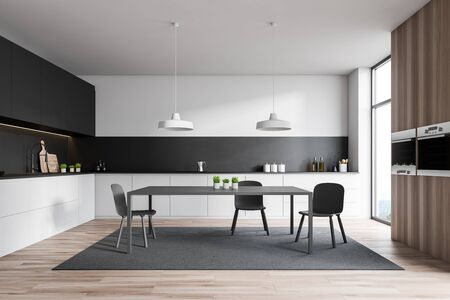 Interior of stylish kitchen with white and black walls, wooden floor, white countertops, gray cupboards, table standing on carpet and wooden cupboard with ovens. 3d rendering Stock Photo
