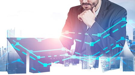 Thoughtful caucasian businessman working with laptop at table over cityscape background with double exposure of graphs. Concept of trading and analytics. Toned image