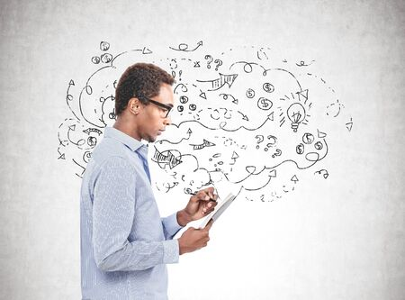 Side view of pensive young African American man in glasses taking notes standing near concrete wall with business goal sketch drawn on it.