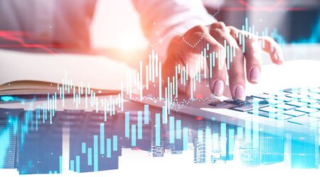 Hand of businesswoman typing on laptop keyboard over cityscape background with double exposure of forex graphs. Concept of trading. Toned image blurred Banco de Imagens