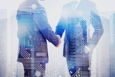 Close up of two businessmen shaking hands in city with double exposure of circuit interface. Concept of partnership and hi tech in business. Toned image 写真素材