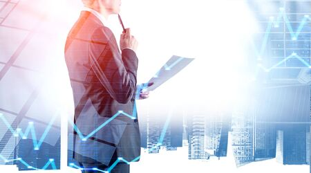 Pensive young businessman with document and pen standing over cityscape background with double exposure of graphs. Stock market concept. Toned image