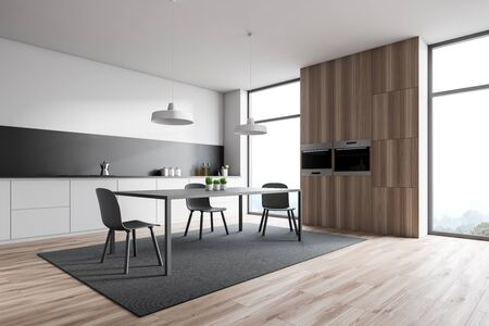 Corner of loft kitchen with white walls, wooden floor, white countertops, dining table standing on carpet and wooden cupboard with ovens. 3d rendering