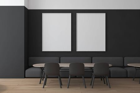 Interior of modern restaurant with black and white walls, wooden floor, gray sofas and chairs standing near wooden tables and two mock up posters on wall. 3d rendering Фото со стока