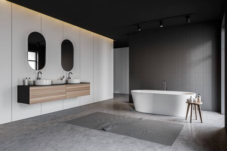 Corner of stylish bathroom with gray tile and white walls, concrete floor, white bathtub with carpet near it and double sink with mirrors on wooden countertop. 3d rendering