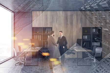 Two businessmen shaking hands in modern open space office with gray walls, wooden bookcases and rows of computer desks. Toned image double exposure