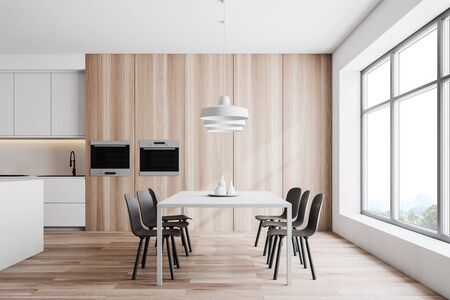 Interior of modern kitchen and dining room with white walls, wooden floor, white countertops and ovens and white table with chairs. 3d rendering Stock Photo