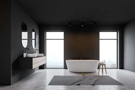 Interior of loft bathroom with gray and gray tile walls, concrete floor, white bathtub standing near window and double sink with two mirrors above it. 3d rendering