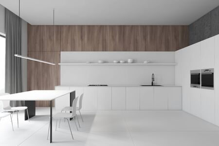 Interior of stylish kitchen with concrete and wooden walls, white countertops with sink and cooker, white cupboard with two ovens and table with white chairs. 3d rendering