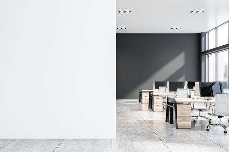 Gray open space office with concrete floor and rows of wooden computer desks. Mock up wall to the left. Concept of advertising. 3d rendering Stok Fotoğraf