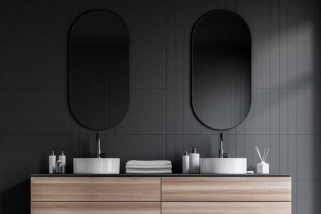 Close up of double bathroom sink standing on wooden countertop with towels on it and oblong mirrors above it in room with gray tile walls. 3d rendering