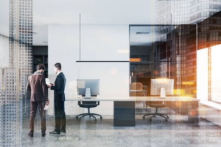 Two young businessmen discussing documents in modern office with white walls, concrete floor and long computer table with black chairs. Toned image double exposure
