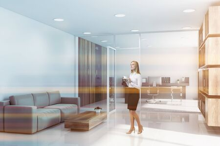 Thoughtful blonde businesswoman standing near CEO office with lounge area. Comfortable sofa near coffee table. Corporate lifestyle concept. Toned image Reklamní fotografie