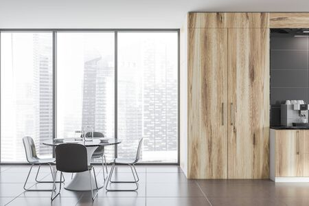 Interior of loft kitchen with gray walls, tiled floors, panoramic window with cityscape, wooden countertops and cupboards and round table with chairs. 3d rendering Stock Photo - 124974960