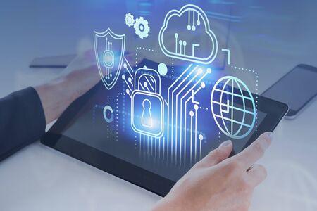 Manos de empresaria hloding tablet PC en mesa de oficina con doble exposición de interfaz de seguridad cibernética. Concepto de protección de datos en las empresas. Imagen tonificada