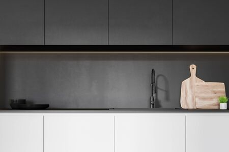 Close up of white kitchen countertop with built in sink, cutting board and dishes standing on it and dark gray cupboards above it. 3d rendering