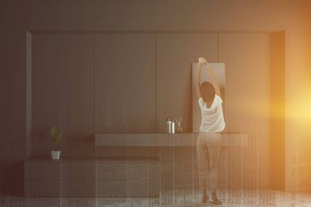 Rear view of woman in pajamas standing in modern bathroom interior with gray walls, concrete floor and gray sink with mirror. Toned image double exposure Stock Photo