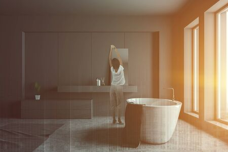 Rear view of woman in pajamas standing in modern bathroom interior with gray walls, concrete floor, white bathtub and gray sink with mirror. Toned image double exposure