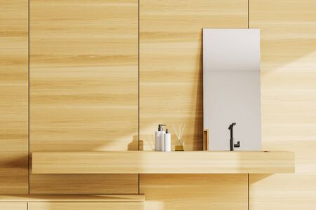 Close up of wooden bathroom sink standing in modern bathroom with wooden walls and vertical mirror. 3d rendering