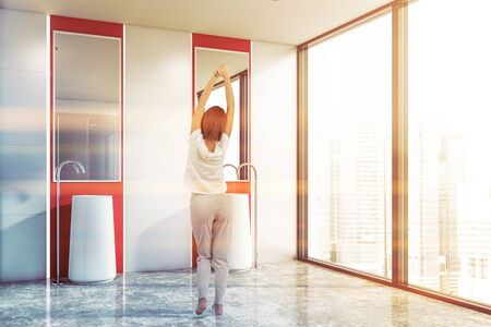Rear view of woman in pajamas standing in white and red bathroom interior with tiled floor, panoramic window and double sink with mirrors above it. Toned image Banco de Imagens