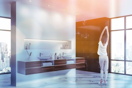 Rear view of woman in pajamas standing in modern bathroom corner with white and black marble walls, white marble floor and double sink with shelf above it. Toned image Stock Photo