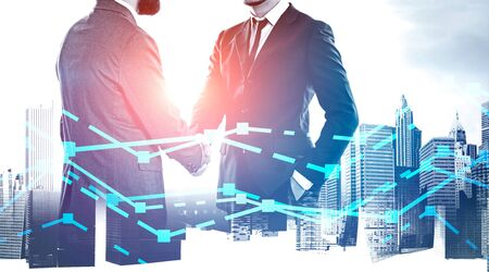 Two young businessmen shaking hands over cityscape background with double exposure of graphs. Concept of trading and partnership. Toned image