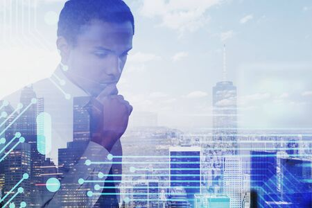 Pensive African American businessman standing over cityscape background with double exposure of circuit interface. Concept of hi tech startup. Toned image