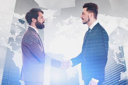 Two young businessmen shaking hands in modern city with double exposure of world map hologram. Concept of international business partnership. Toned image 写真素材