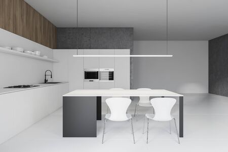 Interior of modern kitchen with white and concrete walls, white countertops with sink and cooker, two ovens and gray and white table with chairs. 3d rendering Stock Photo