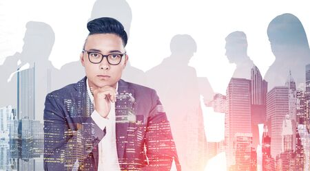 Thoughtful Asian businessman in glasses looking at camera. Double exposure of cityscape and silhouettes of business people. Concept of leadership. Toned image