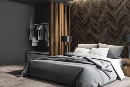Corner of modern bedroom with gray and dark wooden walls, wooden floor, master bed with round bedside tables with lamps and wardrobe with clothes and boxes. 3d rendering