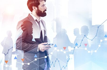 Side view of thoughtful young businessman with smartphone standing over cityscape background with double exposure of his team and graphs. Toned image