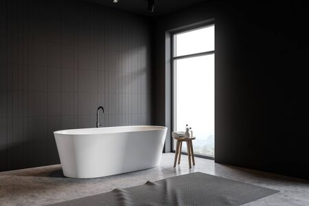 Corner of minimalistic bathroom with gray tile and gray walls, comfortable white bathtub, chair with shampoos and towels and loft window. 3d rendering