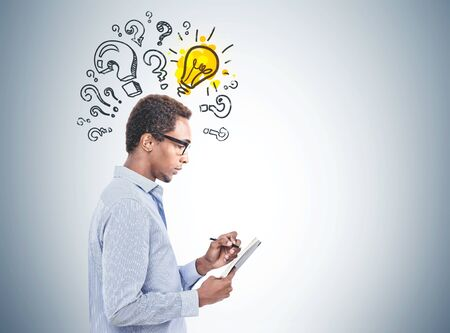 Side view of pensive young African American man in glasses taking notes standing near gray wall with question marks and light bulb drawn on it. Concept of good idea. Mock up Stock fotó