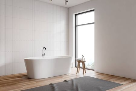 Corner of minimalistic bathroom with white tile and white walls, comfortable white bathtub, chair with shampoos and towels and loft window. 3d rendering