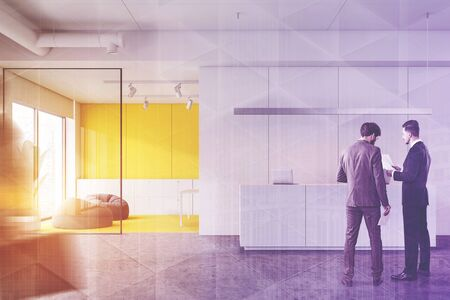 Business people discussing documents in modern industrial style office with white and yellow walls, reception desk and waiting area with pouffes. Toned image double exposure blurred