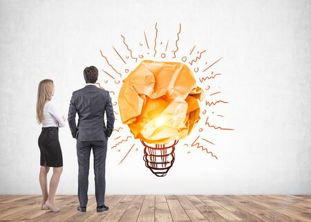 Rear view of businessman and blonde businesswoman looking at lightbulb sketch on concrete wall. Concept of good idea