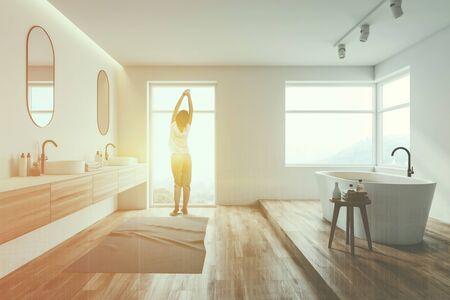 Vista posteriore della donna in pigiama in piedi all'interno di un lussuoso bagno bianco con pavimento in legno, ampie finestre, comoda vasca da bagno e doppio lavabo. Doppia esposizione dell'immagine tonica