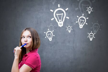 Portrait of young caucasian woman with long fair hair wearing pink polo shirt, holding marker and thinking standing near blackboard with lightbulbs drawn on it. Concept of good idea