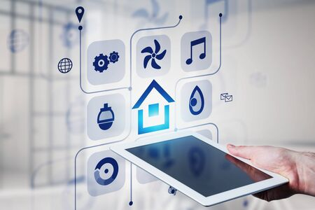 Man hand with tablet computer with double exposure of smart home icons over blurred room background. Concept of automation