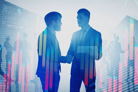 Two young businessmen shaking hands in city with colleagues in background and double exposure of graphs. Concept of partnership and stock market. Toned image