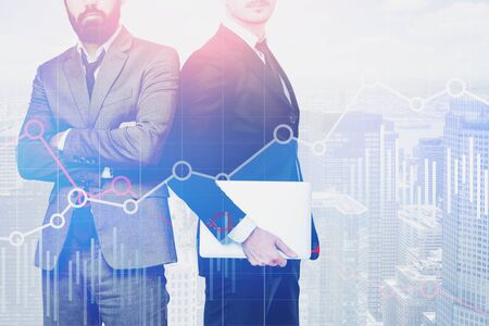 Businessman with laptop and his confident bearded colleague standing over cityscape background with double exposure of diagrams. Concept of trading. Toned image