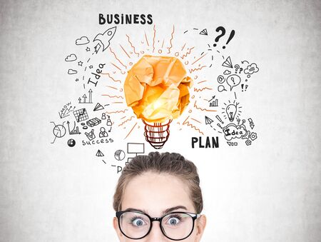 Astonished young woman in glasses standing near concrete wall with business idea sketch drawn on it. Concept of business planning