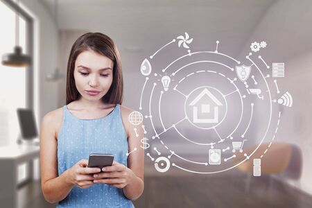 Young woman in blue dress looking at her smartphone standing in blurred bedroom with double exposure of smart home interface. Concept of automation